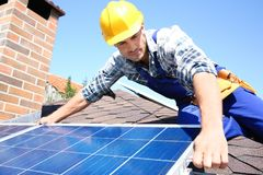 Worker installing solar panels. Outdoors Stock Photo