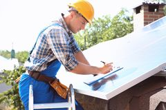 Worker installing solar panels. Outdoors Stock Images