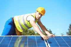 Worker installing solar panels. Outdoors Stock Image