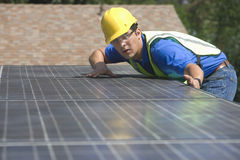 Worker Installing Solar Panels On Rooftop. Young maintenance worker installing solar panels on rooftop Stock Photo