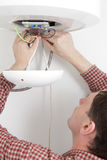 Worker installing a water heater Stock Image
