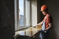 Worker is installing a window sill. Worker is installing a window sill on a polyurethane foam Stock Image
