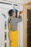 Worker installing wooden door, using polyurethane foam Royalty Free Stock Image