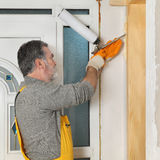 Worker installing wooden door, using polyurethane foam Royalty Free Stock Photography