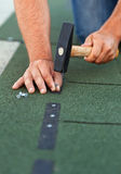 Worker installs bitumen roof shingles - closeup Stock Images