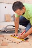 Worker installs ceramic tiles Stock Images