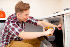 Worker installs a electric cooker Stock Image