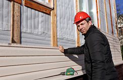 A worker installs panels beige siding on the facade Royalty Free Stock Image