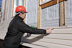 A worker installs panels beige siding on the facade Royalty Free Stock Photography