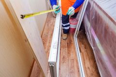 The worker installs plastic windows and doors. The worker tools installs plastic windows and doors royalty free stock photo