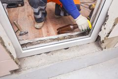 The worker installs plastic windows and doors. The worker tools installs plastic windows and doors royalty free stock photos
