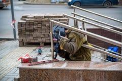 Worker installs rails to underground passage. View of man in worker`s uniform mounting metal rails to underground passage in street Stock Photos