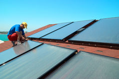 Worker installs solar panels Royalty Free Stock Image