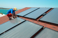 Worker installs solar panels Stock Image