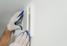Worker installs ventilation grille. Worker installs ventilation grille on the wall Royalty Free Stock Photography