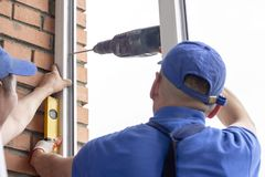 Worker installs windows craftsmen screw frame to the wall Repair in high-rise building. Worker installs windows craftsmen screw the frame to the wall Repair in a royalty free stock image