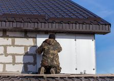 Worker insulates the walls of the house with plastic panels royalty free stock image