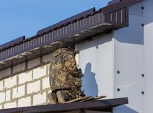 Worker insulates the walls of the house with plastic panels royalty free stock photo
