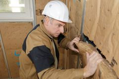 Worker insulates the walls. Insulation royalty free stock photography
