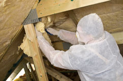 Worker insulating a roof Stock Photos