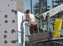 The worker insulation the facade of the building. Chortkiv - Ternopil - Ukraine - August 14, 2018. The worker performs work insulation the facade of the stock photos