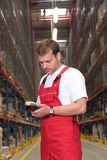Worker with inventory device. A worker with scanner in a factory maintaining stocks of finished products on the shelves in a storeroom stock photo