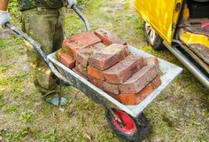 Worker Is Transporting A Brick In A Wheelbarrow Royalty Free Stock Photography