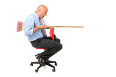 Worker jousting. Worker in a chair jousting with a broom Royalty Free Stock Photo