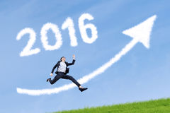 Worker jumps with numbers 2016 and upward arrow in sky Royalty Free Stock Photo
