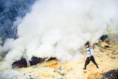 Worker at Kawah Ijen breaking solidified sulpher in small pieces with a metal rod Stock Photos