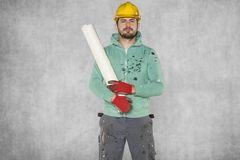 The worker keeps building plans on his shoulder. Protective helmet on the head Stock Photos