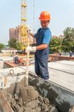 Worker kneads solution for bricklayers. Tyumen, Russia - July 31, 2013: JSC Mostostroy-11. Construction of 18-storeyed brick residental house at the intersection Stock Images