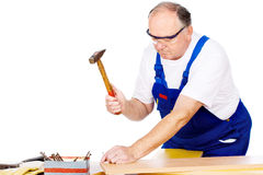 Worker knocking the nail in board Stock Images