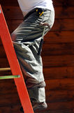 Worker on ladder. Main doing roof repairs steadies himself as he climbs ladder stock image