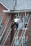 Worker on a ladder. Man on a ladder, fixing eaves-trough stock image