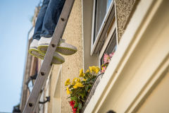 Worker on ladder. Man or woman on ladder. Closeup. Only his feet in the picture Stock Photography