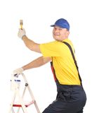 Worker on ladder with paintbrush. Stock Photography