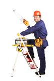Worker on ladder with saw. Royalty Free Stock Photography