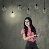 Worker with laptop looking at light bulb Stock Image