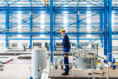 Worker in large metal workshop checking work. Worker in large metal workshop or factory checking work standing on large machine Royalty Free Stock Photography