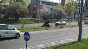 Worker lawn cut road cars. Worker drive lawn cut tractor between street road lines and cars go arround circa May 2013 in Vilnius, Lithuania. City center stock video footage