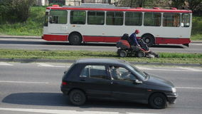 Worker lawn cut road cars. Worker drive lawn cut tractor between street road lines and cars go arround circa May 2013 in Vilnius, Lithuania stock footage