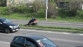 Worker lawn mower road. Worker drive lawn grass cut tractor mower between street road lines and cars go around circa May 2013 in Vilnius. City center environment stock video footage
