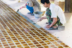 Worker is laying brown tile on the floor Royalty Free Stock Photo