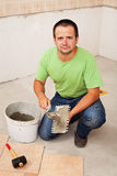 Worker laying ceramic floor tiles Stock Photo