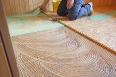 Worker laying insulation layer and spreading adhesive primer Royalty Free Stock Photos