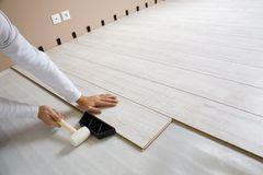 Worker laying laminated. Worker laying a floor with laminated flooring boards royalty free stock photos