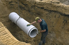 Worker laying new sewer pipe in slot in the street Stock Photo