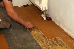 Worker laying parquet flooring. Worker installing wooden laminate flooring. Parquet flooring. Worker laying parquet flooring stock images