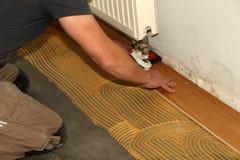 Worker laying parquet flooring. Worker installing wooden laminate flooring. Parquet flooring. Worker laying parquet flooring stock image